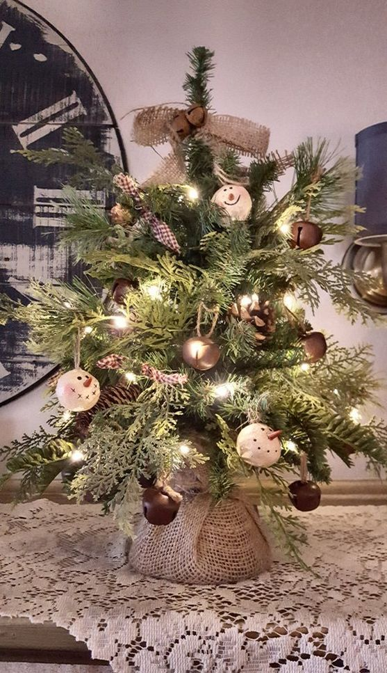 a rustic vintage tabletop Christmas tree with lights, large bells, snowman ornaments, burlap bows and garlands