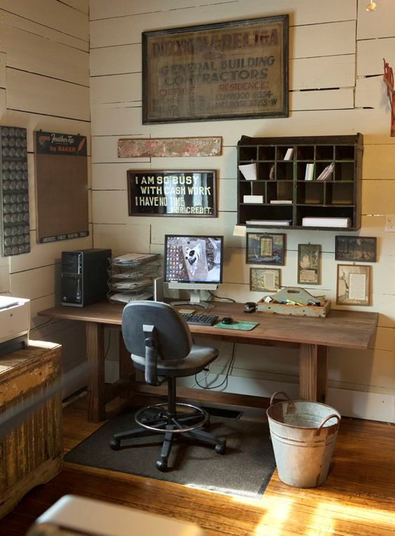 a shabby rustic home office with plank walls, wooden furniture, a gallery wall with artworks and a storage piece and a bucket as a trash can
