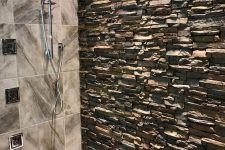 a shower space with pebbles on the floor, grey marble tiles and an accent wall of manufactured stone for a warm feeling here