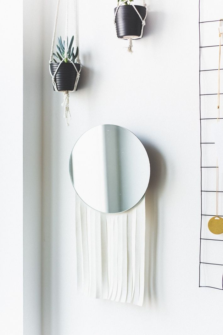 a simple round IKEA mirror hack with long white fringe to make it look more boho-like