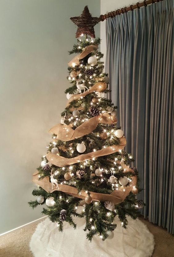 a simple rustic Christmas tree with lights, white and gold ornaments, burlap ribbons, snowy pinecones, a vine star topper