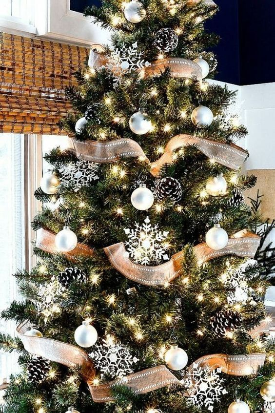 a simple rustic Christmas tree with white ornaments, snowy pinecones, snowflakes and lights