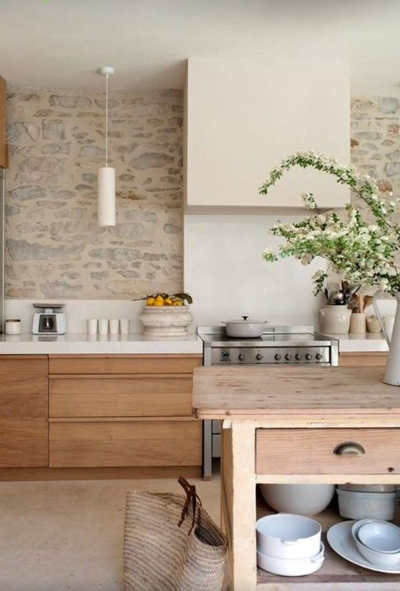 a sleek contemporary kitchen with a neutral painted stone wall that gives it a rich, a bit rustic feel and look