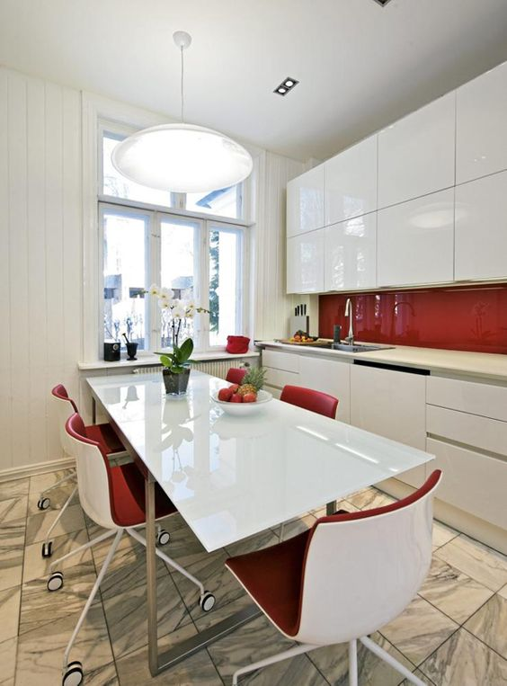 a sleek white kitchen with plain cabinets and a sleek red backsplash plus red chairs is a bold idea for a minimalism fan