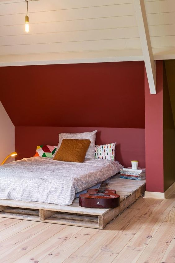 a small attic bedroom with a burgundy statement wall, a simple pallet bed, bright printed bedding and books