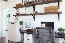 a small farmhouse shred home office with a black and white shared desk, rustic shelves on the wall and mismatching chairs for comfort