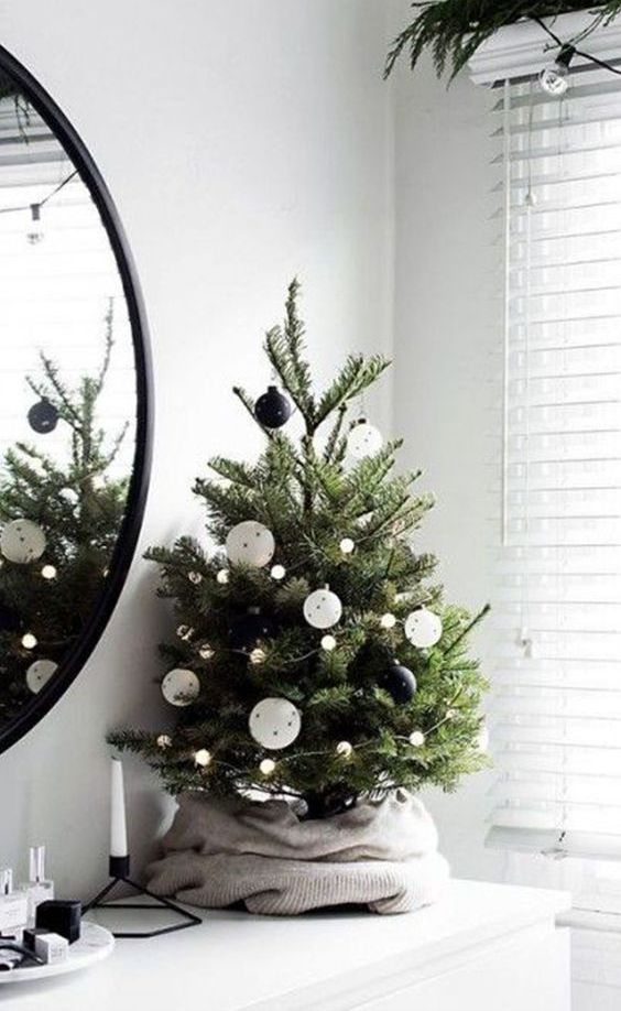 a small modern Christmas tree with lights and black and white ornaments wrapped with a sweater is a lovely idea for any room