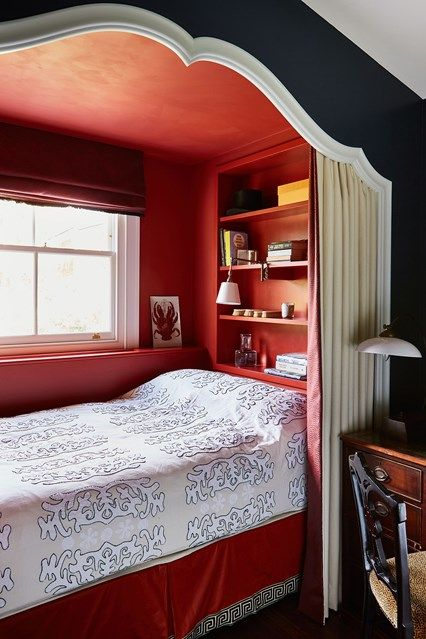 a small niche bedroom with red walls, built in shelves, printed bedding and a curtain for privacy is very chic