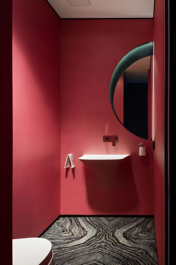 a small red powder room with a round lit up mirror, a floating vanity, a marble tile floor is modern and very chic and stylish