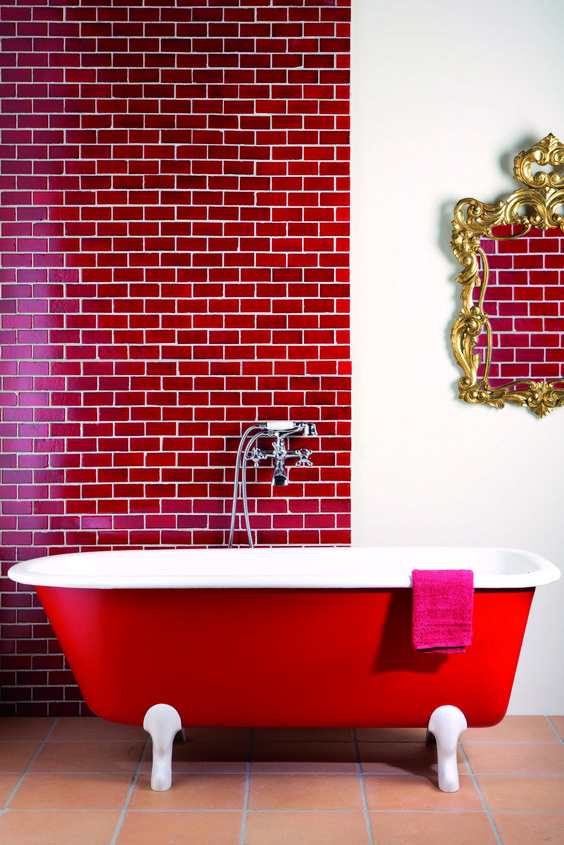 a stunning bathroom accented with a red subway tile wall and a red bathtub, a refined mirror is a bold and refined space
