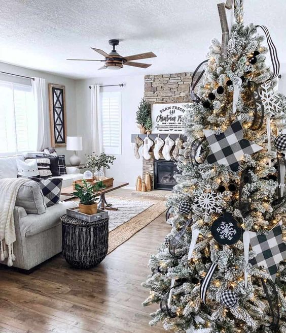 a stylish and chic flocked famrhouse Christmas tree with lights, printed black and white ornaments and snowflakes is wow