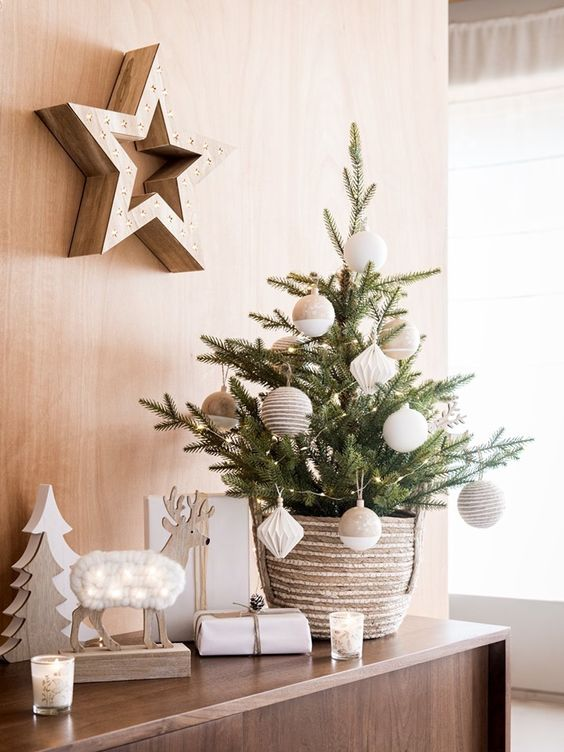 a stylish and simple tabletop Christmas tree decorated with twine and color block neutral ornaments and put into a crochet basket