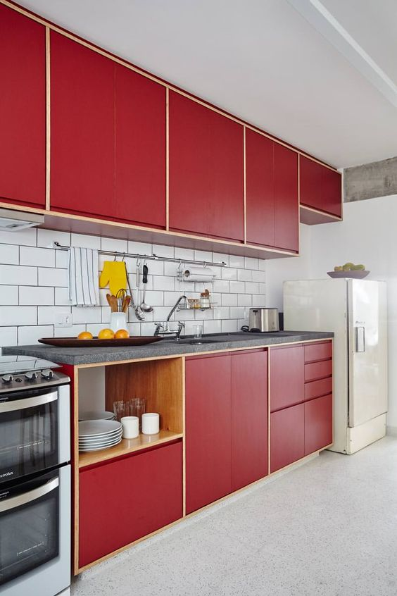a stylish bold mid-century modern kitchen with red plywood cabinets and a white subway tile backsplash and a white fridge