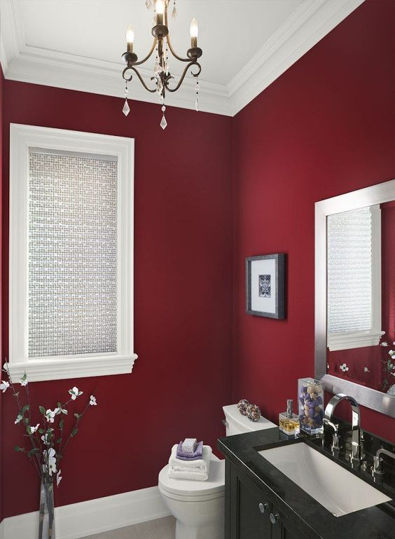 a stylish burgundy bathroom with a black vanity, a refined chandelier and a mirror plus an artwork is chic