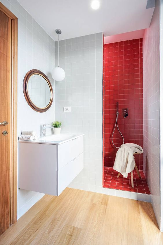 a stylish contemporary bathroom with a lainate floor, a red tile shower space, a round mirror and a floating vanity of white color