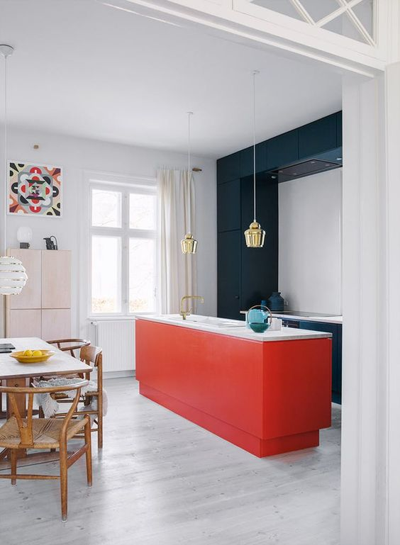 a stylish contemporary kitchen with sleek navy cabinets and a red kitchen island plus white countertops and gold pendant lamps