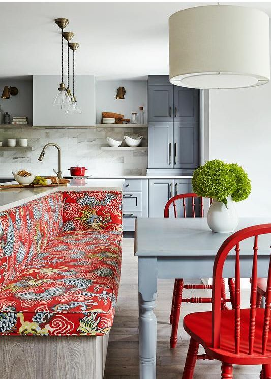 a stylish grey kitchen with a marble tile backsplash, a red upholstered bench and chairs plys some cookware for bold accents