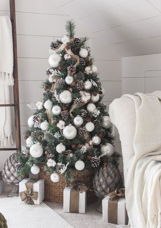 a stylish modern and a bit rustic Christmas tree with large pearly ornaments, snowy pinecones, burlap ribbons and bells