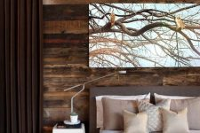 a stylish modern bedroom in shades of brown is added interest with a reclaimed wood wall that brings coziness and warmth to the room