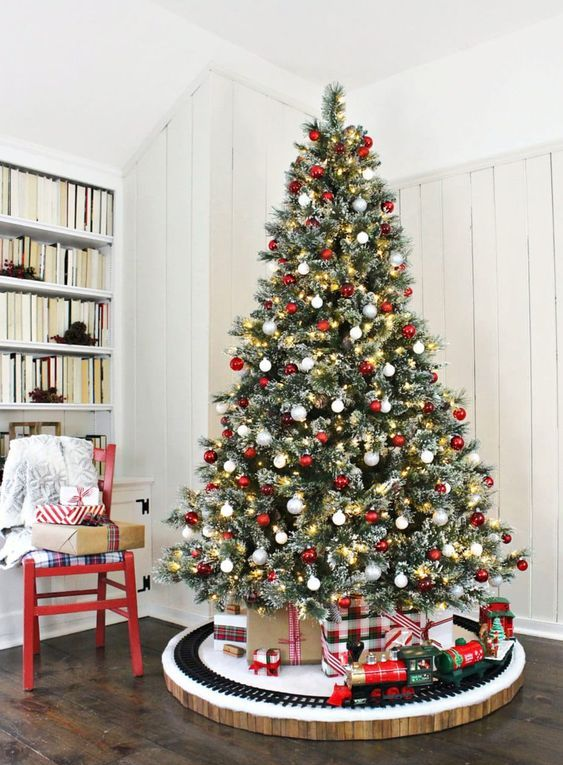 a stylish modern yet traditional Christmas tree with lights and red and white ornaments is a fresh take on classics