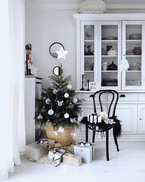 a stylish small Christmas tree with white and sheer ornaments put into a basket is a lovely and beautiful idea