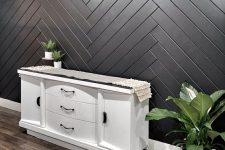 a stylish wooden accent wall clad ina herringbone pattern and painted black will make a cool statement in your entryway