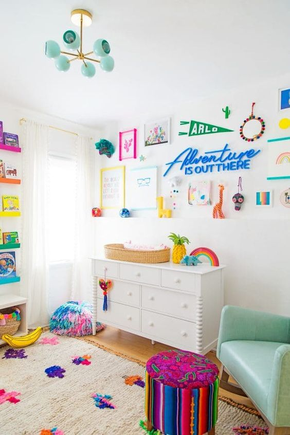 a super bold nursery with white furniture, a mint rocker, a bright gallery wall with artworks, signs and other stuff, a bold rug and books