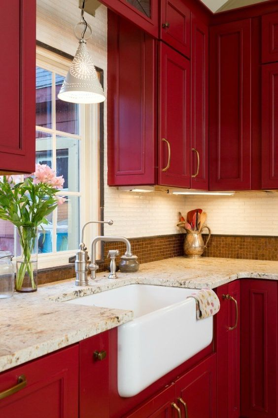 a super bold red vintage kitchen with two types of tiles on the backsplash and stone countertops looks very chic and elegant