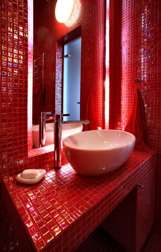 a super bright red bathroom fully clad with mini tiles, a round sink, some modern appliances and round lights here and there