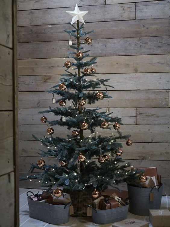 a super elegant modern Christmas tree decorated only with copper ornaments and with gifts in buckets