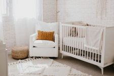 a sweet neutral nursery with wallpaper walls, white furniture, layered rugs, a pink tassel chandelier and some pillows