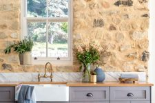 a tan stone accent wall contrasts the lilac cabinets creating a very eye-catchy kitchen with a refined vintage feel
