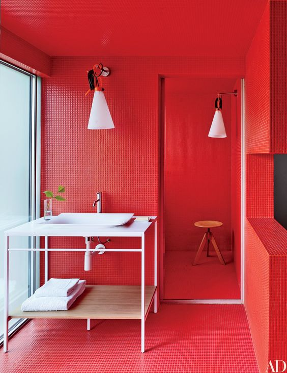 a total red bathroom all clad with tiles, with pendant lamps, an ethereal white vanity and a wooden stool in the shower
