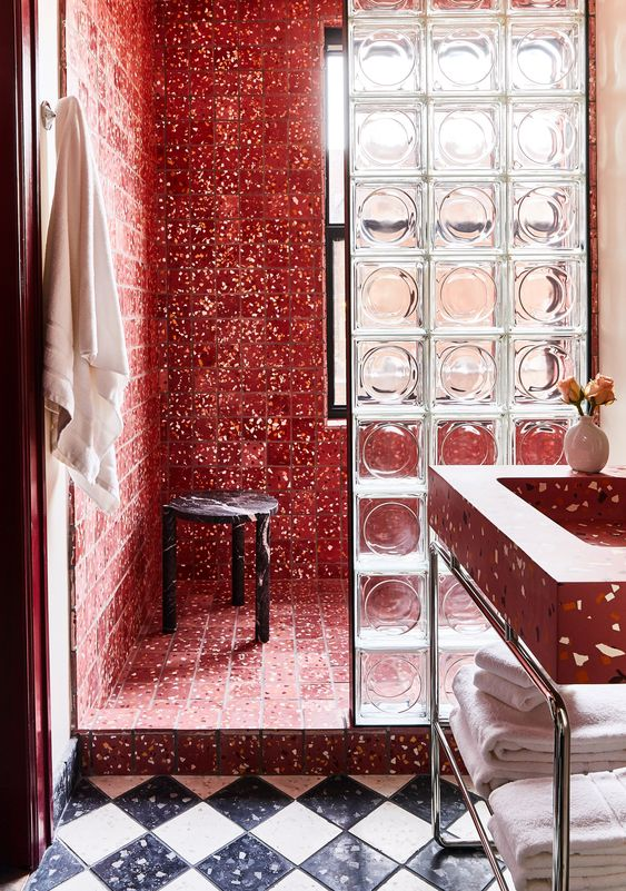 a unique bathroom with a red terrazzo shower space separated with a glass divider, a red terrazzo sink and a black marble stool