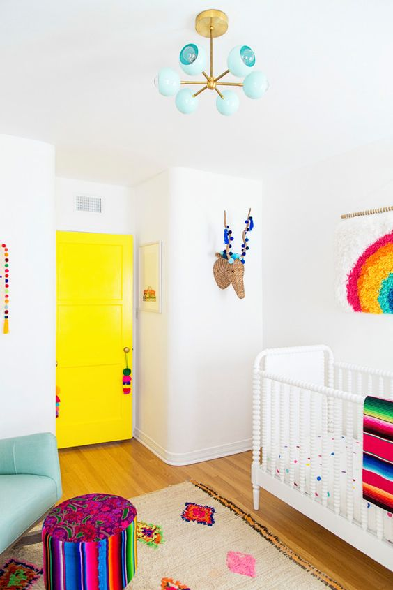 a vibrant nursery with a sunny yellow door, bold printed bedding, a turquoise chandelier and bold artworks and garlands