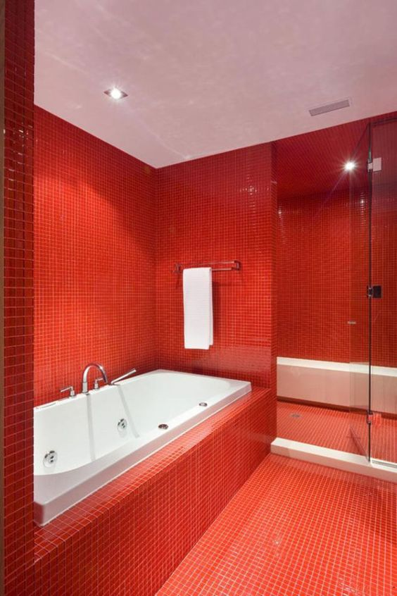 a vibrant red and white bathroom with white appliances and a white bench in the shower space plus red tiles covering the walls and floor