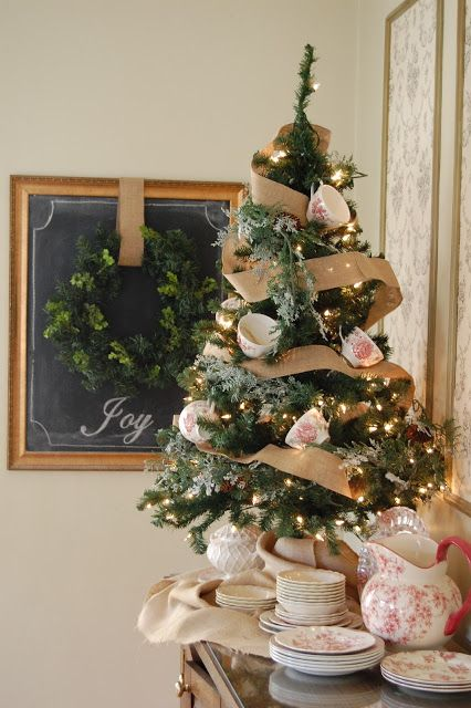 a vintage and rustic tabletop Christmas tree decorated with lights, burlap ribbons and teacups is a lovely idea