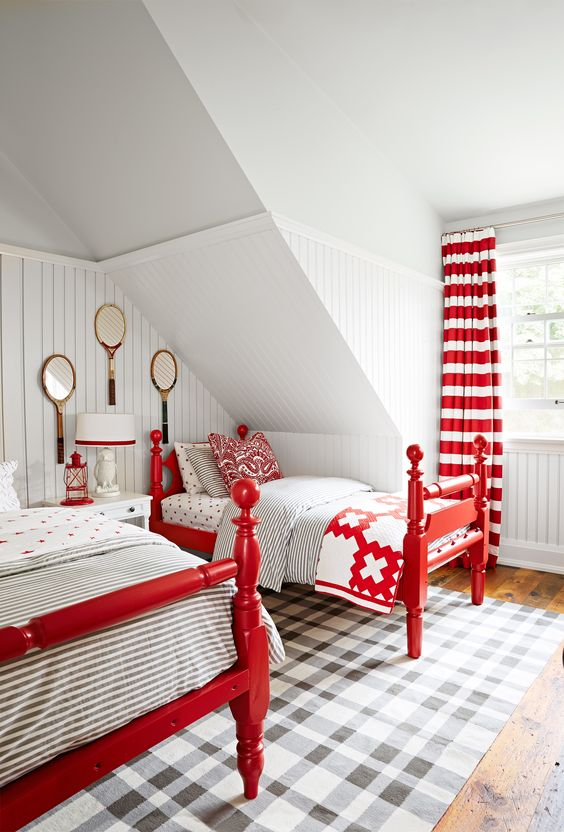 a vintage attic guest bedroom with vintage red beds, striped cutrains, a table lamp and a lantern in red