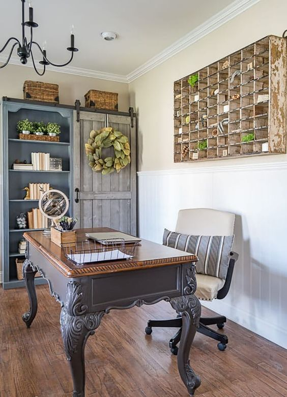 a vintage farmhouse home office with a grey vintage desk, a matching storage unit, a white chair and a large storage piece on the wall