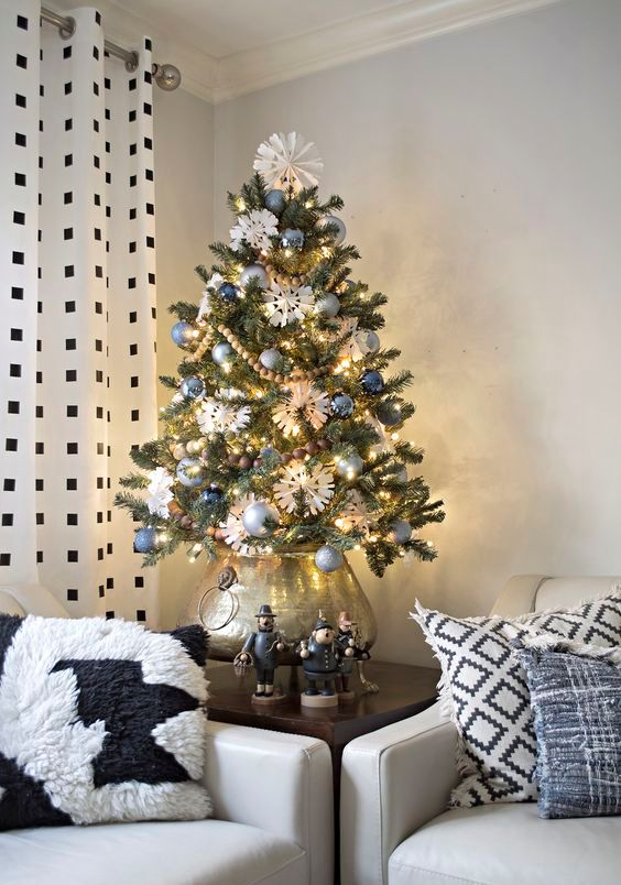 a vintage-inspired tabletop Christmas tree with blue and silver ornaments, wooden bead garlands, lights and paper snowflakes put into a silver pot