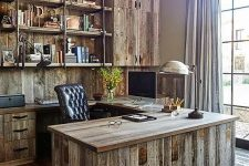 a vintage meets rustic home office with a wall and furniture fully made of reclaimed wood, a reclaimed wood floor, a metal chandelier and a leather chair
