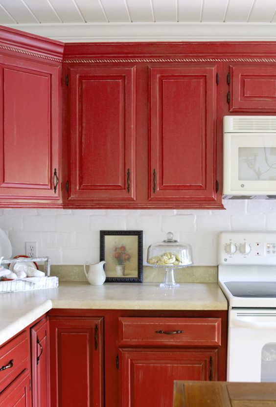 a vintage red kitchen with a white tile backsplash, stone countertops and white appliances and vintage handles is chic