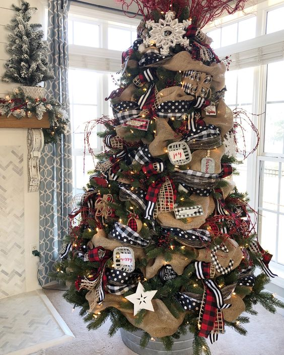 a vintage rustic Christmas tree decorated with polka dot and plaid ribbons, burlap ribbons, lights, stars and snowflakes plusa bold topper
