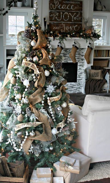 a vintage rustic Christmas tree with lights, beaded garlands, pinecones, burlap ribbons, white ornaments and snowflakes is lovely