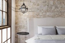 a vintage rustic bedroom with a stone accent wall, elegant furniture and a veyr eye-catchy pendant lamp over it
