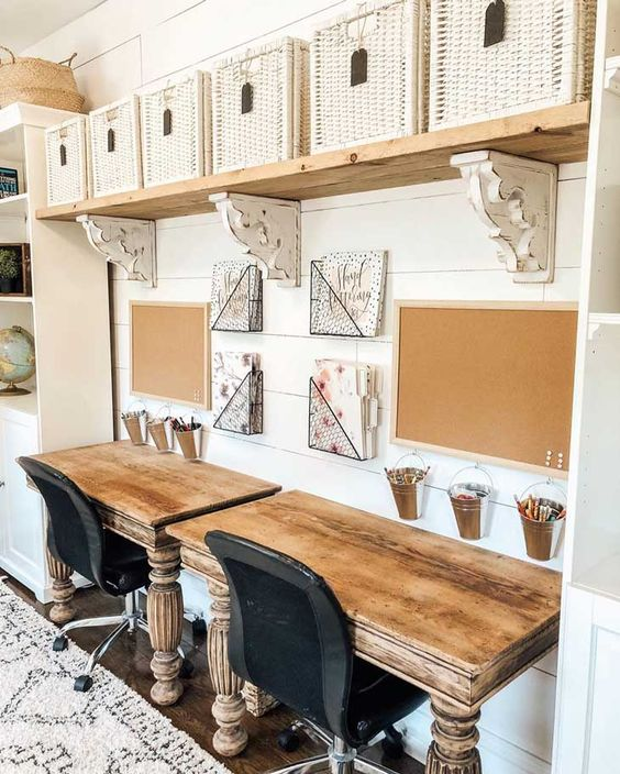 a vintage rustic home office with shabby wooden desks, a shelf with white baskets, black chairs and boards for drawing or attaching notes
