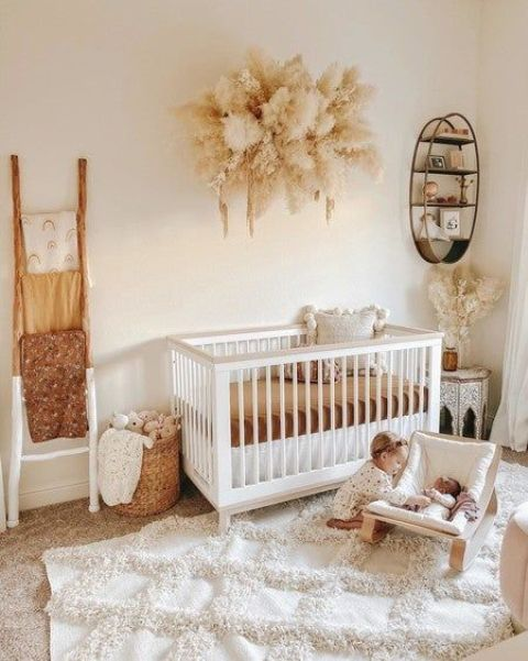 a warm boho nursery with white and neutral wooden furniture, a ladder, a dried grass overhead installation and some Moroccan touches