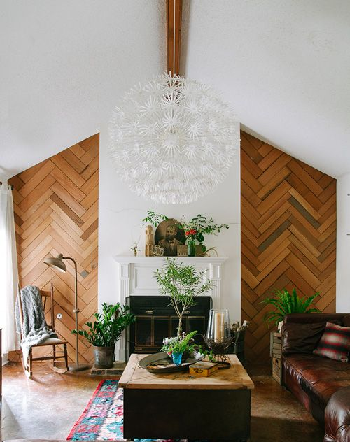 a welcoming mid-century modern living room with a stained herringbone wooden wall, a fireplace, a leather sofa and a colorful rug