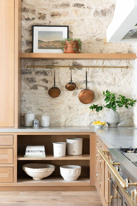 a welcoming neutral kitchen with a whitewashed stone wall and light colored wooden cabinets plus touches of brass