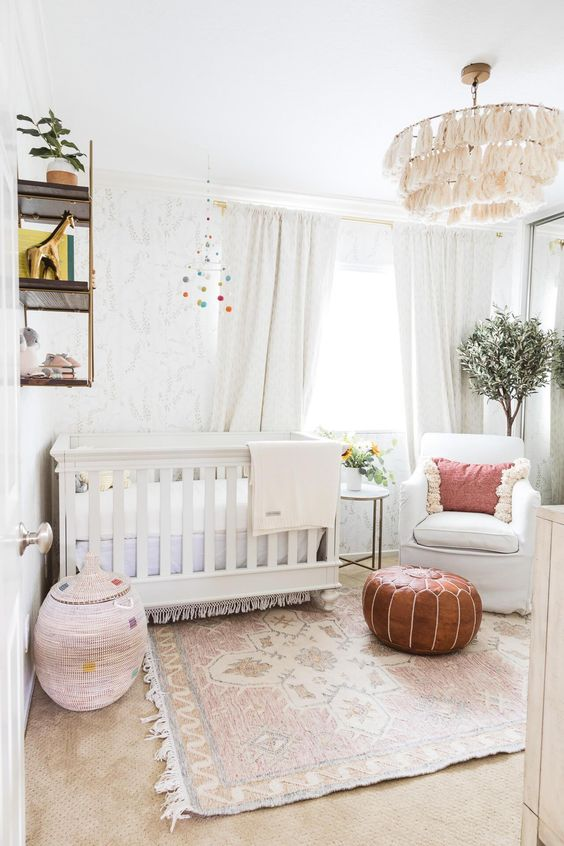 a welcoming neutral nursery with printed wallpaper, white furniture, a tassel chandelier, a leather ottoman and a woven basket plus greenery